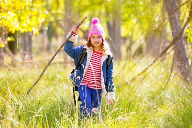 Escursionismo ragazza bambino con zaino nella foresta di pioppo autum