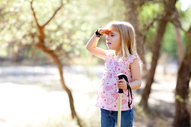 Escursionismo ragazza ragazzino cercando mano nella testa nella foresta
