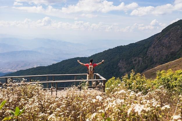 Escursionista che alza le braccia sulla piattaforma panoramica
