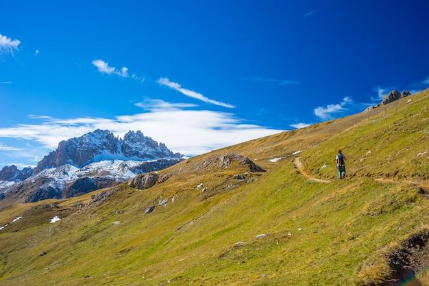 Escursionista che cammina su una valle colorata con splendida vista panoramica e colori vivaci.