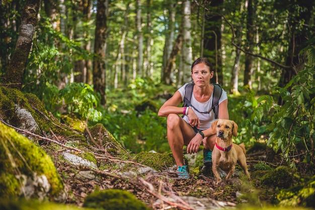 Escursionista con un cane nella foresta