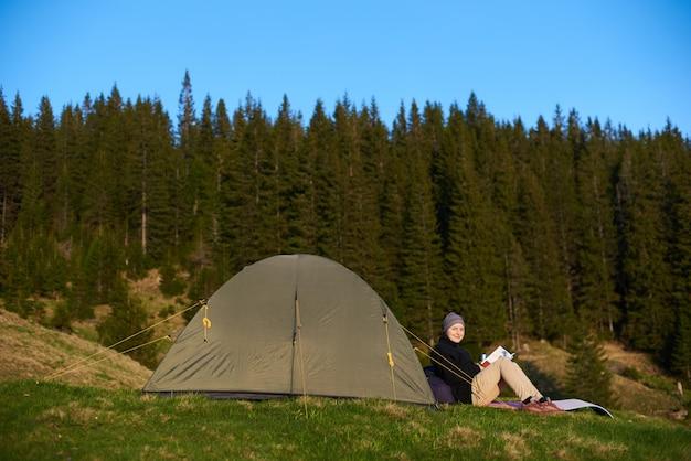 Escursionista donna felice leggendo un libro vicino alla tenda la sera, sorridendo alla telecamera