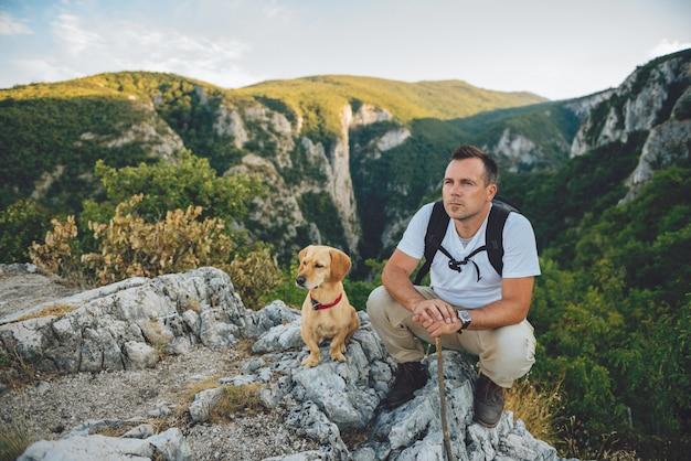 Escursionista e il suo cane seduto sulla cima della montagna