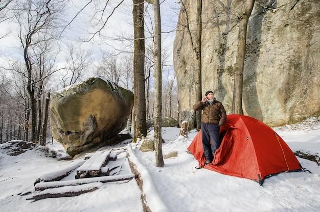 Escursionista maschio quasi la sua tenda rossa in montagna