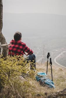 Escursionista rilassato con camicia a scacchi all'aperto