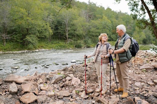 Escursionisti allegri e affettuosi con zaini e bastoncini da trekking che si guardano sul fiume