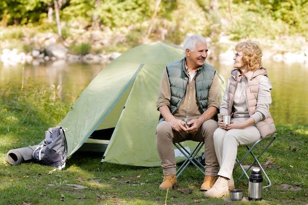 Escursionisti allegri in abbigliamento sportivo che si godono il riposo in tenda in ambiente naturale e conversano con una tazza di tè
