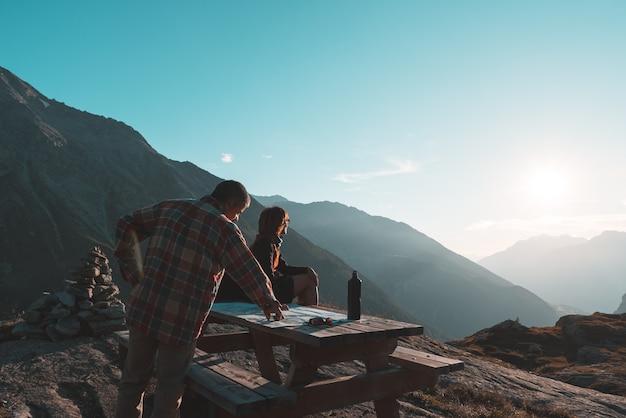 Escursionisti coouple leggendo la mappa di trekking sul tavolo in controluce