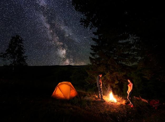 Escursionisti maschili e femminili che si riposano vicino al fuoco vicino alla foresta e incandescente tenda arancione al campeggio in montagna sotto l'incredibile bel cielo stellato che è chiaramente visibile via lattea.