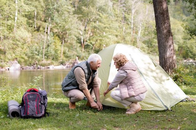 Escursionisti maturi in abbigliamento sportivo che mettono la tenda sull'erba verde in riva al fiume per riposarsi e preparare il cibo