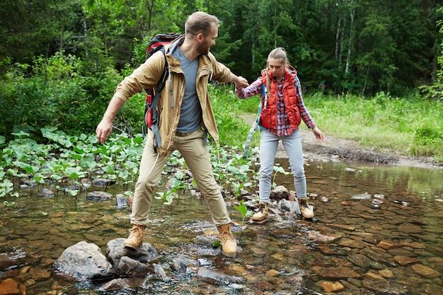 Escursionisti passando fiume