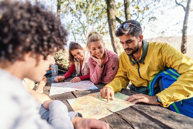 Escursionisti seduti e guardando le mappe