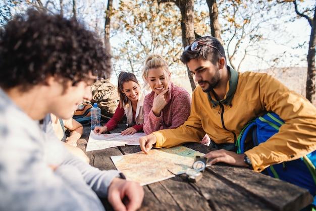Escursionisti seduti sulla panchina al tavolo nel bosco e guardando la mappa