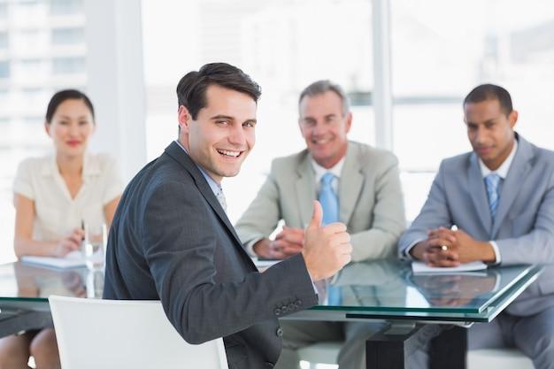 Esecutivo che gesturing i pollici in su con i reclutatori durante il colloquio di lavoro