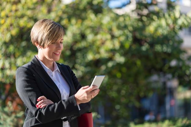 Esecutivo che lavora con un telefono cellulare in strada