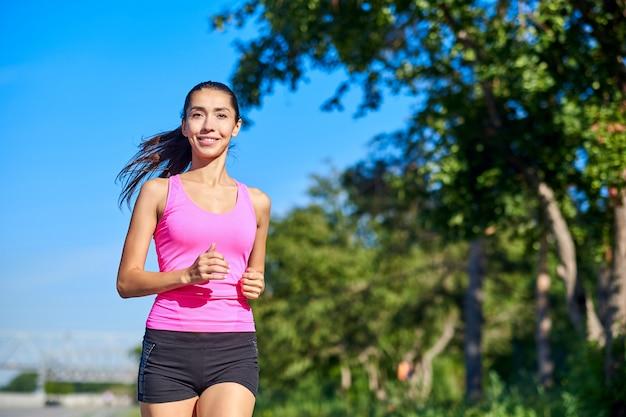 Esecuzione di donna. corridore femminile che pareggia durante l'allenamento all'aperto in un parco. bella ragazza in forma. modello di fitness all'aperto. perdita di peso