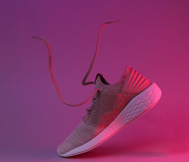 Esecuzione di scarpe sportive con lacci volanti. luce al neon rossa