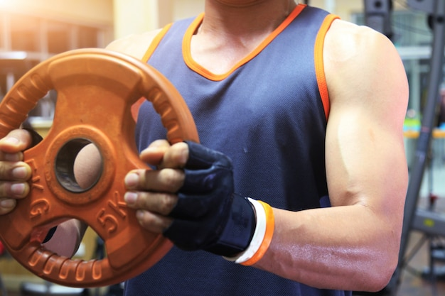 Esercitandosi in palestra, uomo forte che solleva i pesi della mano.