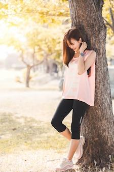Esercitazione di rilassamento della bella giovane donna asiatica in parco