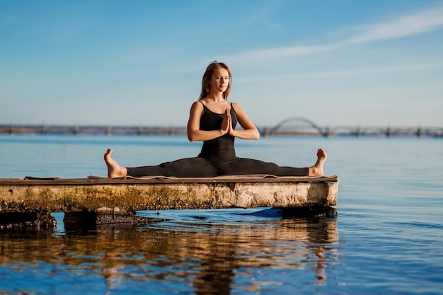 Esercitazione di yoga di pratica della giovane donna al molo di legno calmo con la città sport e ricreazione nella fretta della città