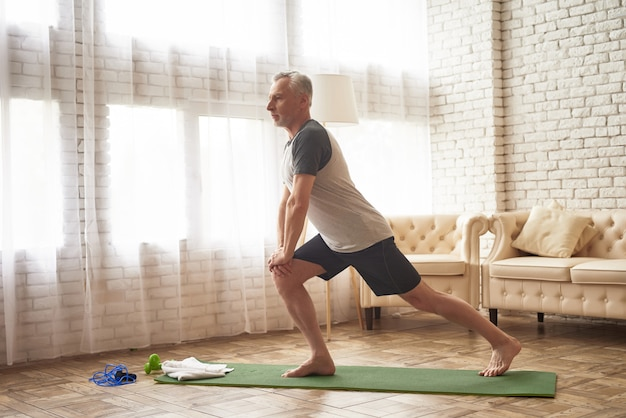 Esercizi di affondo sugli stiramenti dei muscoli della gamba dello stuoino.