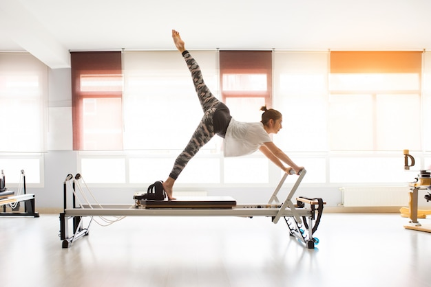 Esercizi di pilates di addestramento della donna in palestra coperta