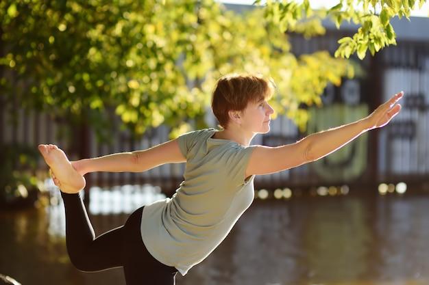Esercizio all'aperto di pratica di yoga della donna matura sulla spiaggia vicino al fiume.