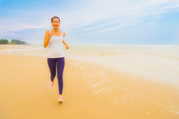 Esercizio asiatico della donna di bello giovane sport del ritratto eseguendo e pareggiando sulla spiaggia e sul mare all'aperto della natura