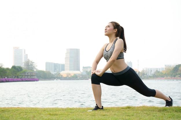 Esercizio asiatico della donna di sport e allungamento dall'yoga in parco sul pascolo