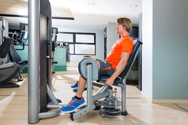 Esercizio biondo dell'uomo di abduzione dell'anca alla palestra dell'interno