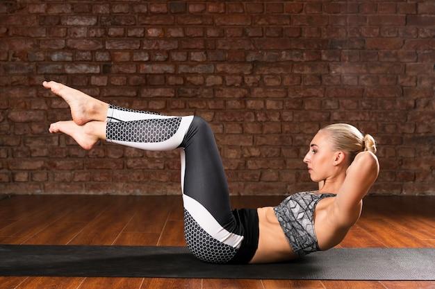 Esercizio complesso di yoga della donna della foto a figura intera