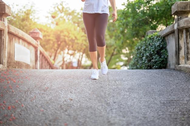Esercizio della donna che cammina nel parco in mattinata.