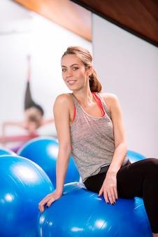 Esercizio della giovane donna con le palle dei pilates