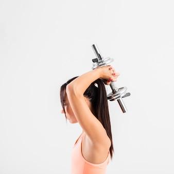 Esercizio della giovane donna di vista laterale con i pesi