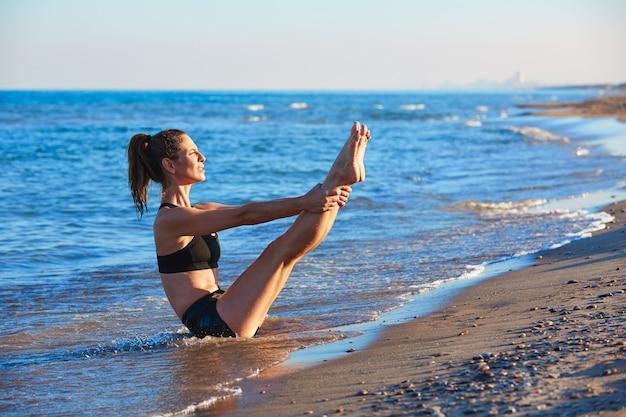 Esercizio di allenamento di yoga di pilates all'aperto sulla spiaggia