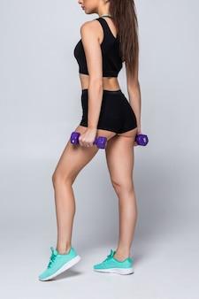Esercizio di allenamento fisico di giovane bella donna con le teste di legno isolate