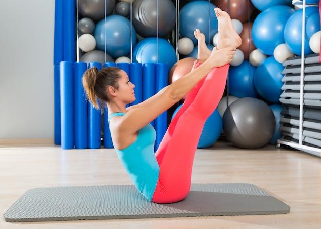 Esercizio di bilanciere di gambe aperte di pilates su donna mat