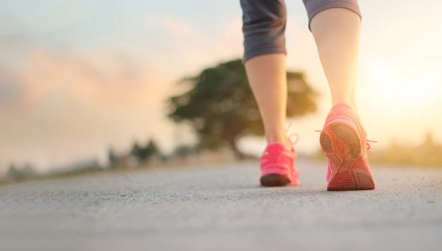 Esercizio di camminata della donna dell'atleta sulla strada rurale nel fondo di tramonto