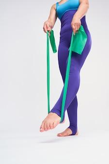 Esercizio di forma fisica della palestra di sport della donna di gomma verde della banda di resistenza di yoga di pilates