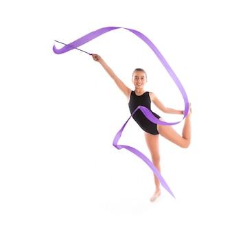 Esercizio di ginnastica ritmica del nastro della ragazza del bambino