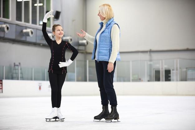 Esercizio di pattinaggio artistico con allenatore