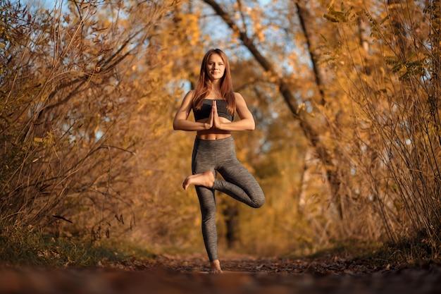 Esercizio di pratica di yoga della giovane donna al parco di autunno con le foglie gialle. stile di vita sportivo e ricreativo