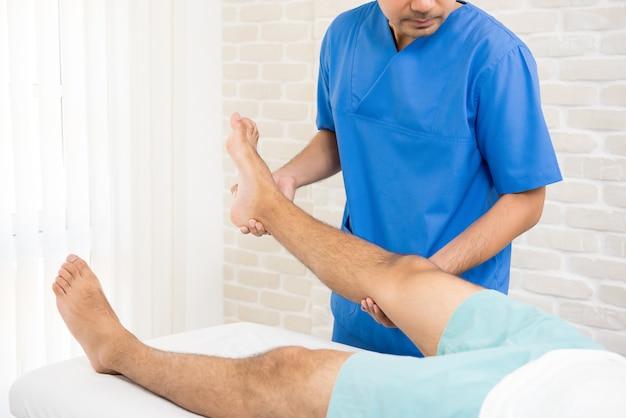 Esercizio di riabilitazione di addestramento del fisioterapista al paziente con gamba rotta