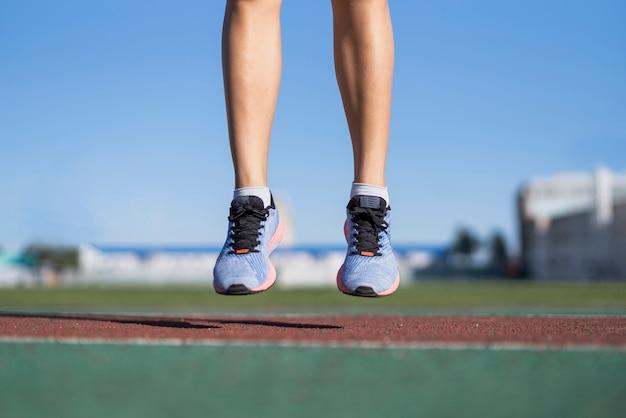 Esercizio di salto della donna allegra del primo piano