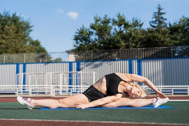 Esercizio di stretching dello stadio sul tappetino