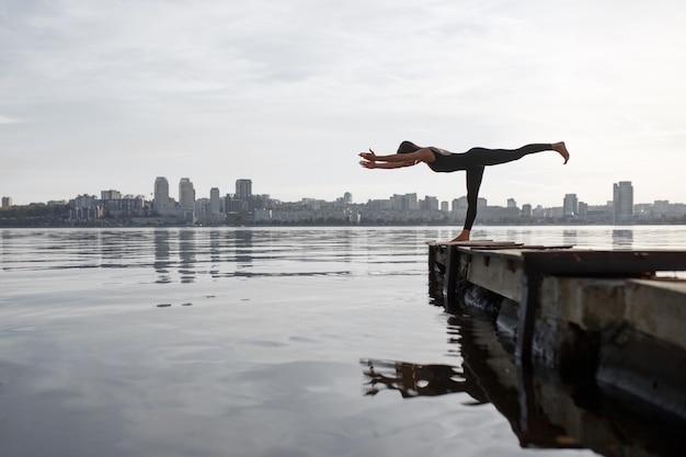Esercizio di yoga di pratica della giovane donna al pilastro di legno calmo con il fondo della città. sport e tempo libero in città