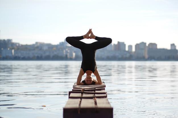 Esercizio di yoga di pratica della giovane donna al pilastro di legno calmo con la città. sport e tempo libero in città