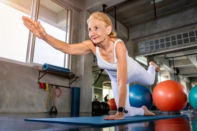 Esercizio facente caucasico di yoga della donna senior alla palestra di forma fisica.