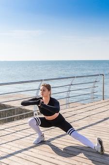 Esercizio facente di modello di allungamento della ragazza femminile di forma fisica