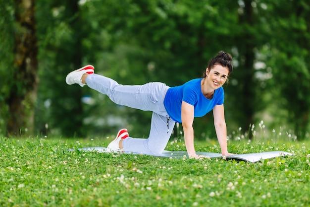 Esercizio facente femminile invecchiato di yoga in parco. yoga di pratica della donna senior outdor